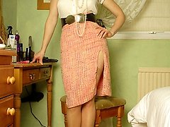 Rebekah freshens up her make up, dressed in fine blouse, tight skirt split to the thigh, showing...