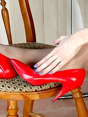 Salacious gal taking off her red high heel shoes and massaging nyloned feet