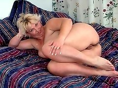 Top heavy mature blonde kneading her plump bazooms and gets down on all fours to show off her ass
