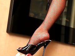Mistress in black fishnet bodystocking lets her slave savor her sweet toes