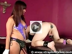Strapon slave is fucked with a big plug stretching his ass for his Mistress