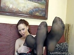 Brunette babe in stockings fingers her shaved pussy on webcam