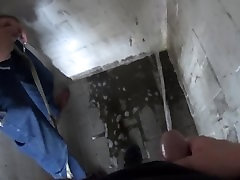 two friends pissing together in the parking garage
