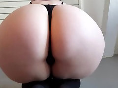 Hot tattooed goth girl sits on her knees and shows her big juicy butt
