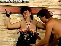 Horny cuckold caged with metal clamps on her big tits gets her nipples sucked