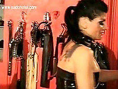 Bending over dirty slave is hit with a whip and spanked on his ass by kis condom wearing mistress