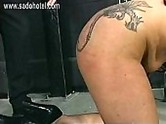 Older slave with big hangin tits and large tattoo on her ass is spanked with a wooden stick her butt