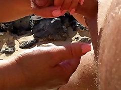 Handjob on beach with cumshot