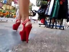 koledžas meitene staigājot publiskā vietā ar platformas augstpapēžu kurpes