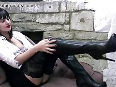 Sexy secretary slowly pulls on her leather thigh boots