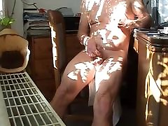 Nude jerking at the desk in front of a window