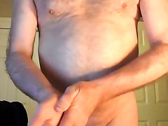 Naked mature man moi putting on lotion after a hot bath.