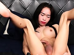 Busty ladyboy tugs on her curved cock
