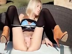 Horny blond in black stockings and high heels fingering