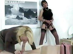 Lady Sonia watches a mature Sandie Caine sucking their slave in a condom