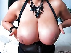 Mature brunette with paker boy boobs is wearing black fishnets and playing with her pussy on the sofa