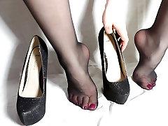 Kaitināt sexy melnas augstpapēžu kurpes un zeķes kājām