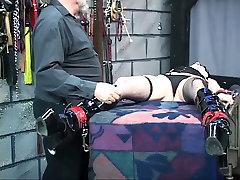 Brunete verdzība geer ir karājās no griestiem ar viņas rokām un kājām