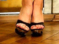 Busty blond beauty\'s stiletto heels almost pierce through slave\'s soft skin