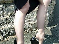 Cute redhead Miranda flashing her shiny stilettos and stockings by the lake
