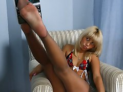 Slim platinum blonde strips to suntan pantyhose showcasing her eatable feet