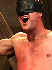 Chained to the St. Andrews Cross, Connor Patricks awaits with leather blindfold impairing his...