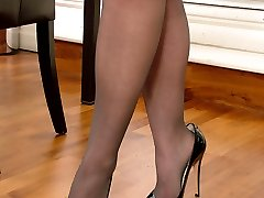 Sexy Anna flashes her stockinged legs and shiny black stilettos as she poses and teases