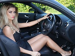 Gorgeous leggy blonde Kathryn is behind the wheel of a powerful Audi sport car, in tall black...