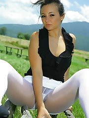Breathtaking brunette in black top, white miniskirt and white pantyhose.