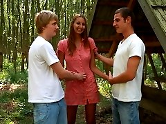 In the middle of the woods, this cute teen turns into a dirty nymph. She practically orders these two studs to tied her hands to the tree and use her in every way possible.