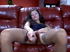 Horny chick spread-eagles on the leather sofa in tan stockings for toy sex