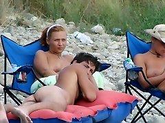 This teenie nudist peels off bare at a public beach