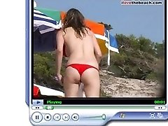 Topless girl with red thong at beach