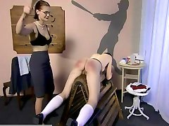 A mean schoolmistress severely correcting a student with a wooden paddle