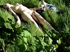 Spy on a nude girl sunbathing in a field