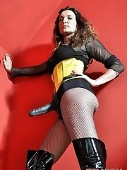 Femdom Strapon Jane plays with her huge strap dildo cock dressed in fishnets, boots and yellow corset