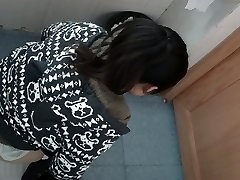 an Asian female in a jumper peeing in public toilet for absolute ages