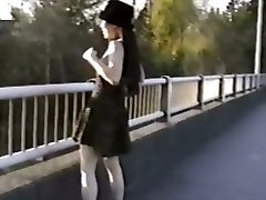 Ασιατικό κορίτσι αναβοσβήνει βυζιά της από γέφυρα