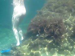 Nudists in the Crimea. Girl underwater in flippers.