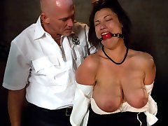 Dana Vixen lives out her fantasy in this BDSM role play update.  This naturally busty woman gets into some trouble while trying to cross the border.  She is thrown into a dirty cell, interrogated and strip searched by Mark Davis.  After finding something hidden up her ass, she is bound, dominated and fucked in the pussy and ass.