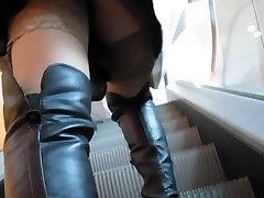 Lady in black leather boots and sunburn stockings on escalator