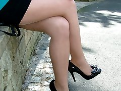 Sexy little blonde showing off her sexy stilettos outdoors