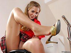 Upskirt gal in glossy pantyhose showing her nice feet while posing on stool
