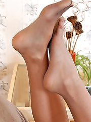 Lusty babe in white boots showing her polished feet clad in lacy pantyhose