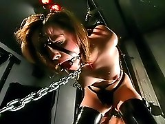 Domina teases a bondaged woman licking her gagged mouth and clasped pussy