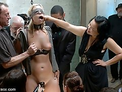 Cute blonde girl shackled and blindfolded in a dungeon Party full of horny men and women one...