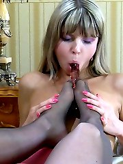 Heated lesbians worship sweet pantyhosed feet before using a glass dildo