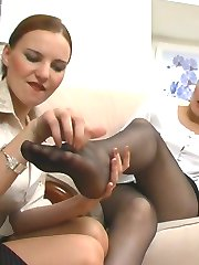 Red hot female co-workers petting each other with their pantyhose clad feet