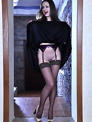 Upskirt teaser in a little black dress and brown stockings flashing goods