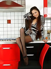 Cutie in black and white dress and matching pantyhose posing in the kitchen